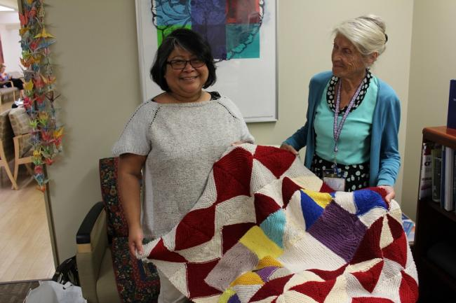 2 women showing a knitted quilt