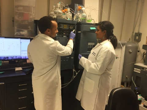 Two people using a lab instrument