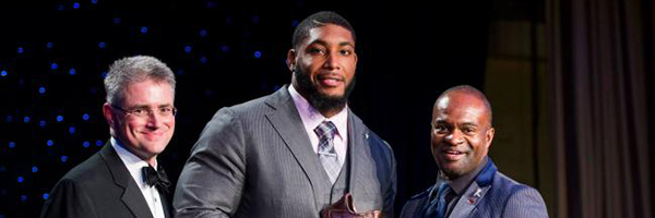 Vincent Lombardi II (left) and DeMaurice Smith (right) pose with honoree Devon Still after he receives his NFL Players Association Georgetown Lombardi Award