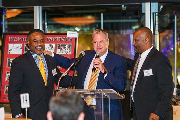 Three men stand at a podium