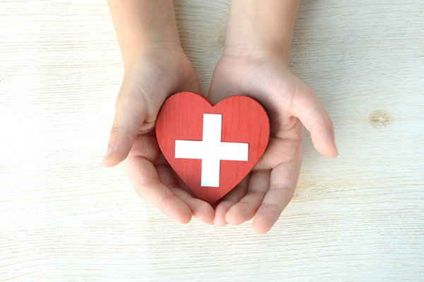 Closeup image of hands holding a a red heart inscribed with a medical cross