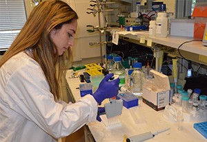 A female student in white lab coat performs an ELISA test