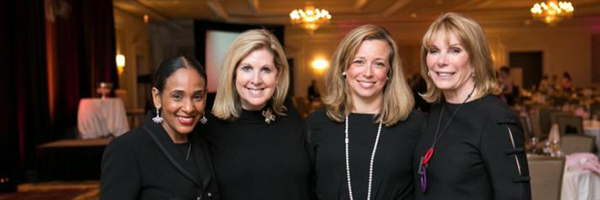 Four women stand side by side and smile at the Women & Wine event