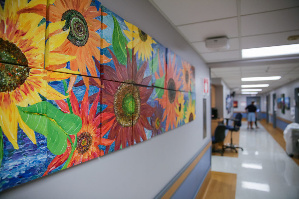 A hospital hallway decorated by a bright mural