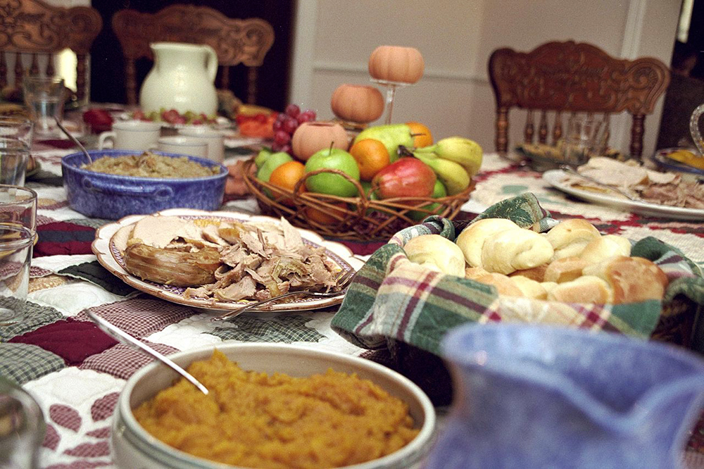 A table spread with dishes of traditional Thanksgiving foods