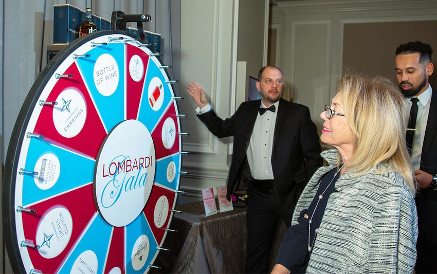A woman regards a prize wheel as two men look on