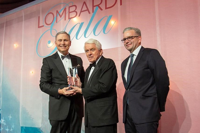 Three men stand together before the Lombardi Gala audience