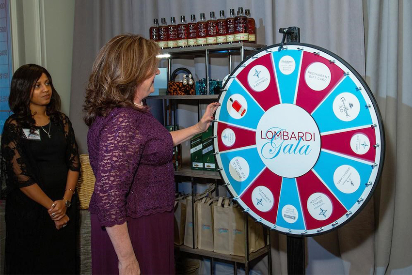 A woman spins a prize wheel as another woman looks on