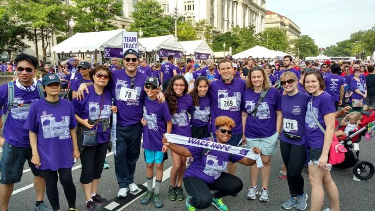 A crowd of people dressed in purple shirts at an event