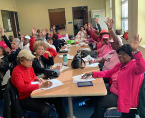 Women sit at tables for a Capital Breast Care Center community workshop
