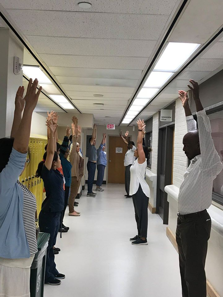 Photo taken of Alison Waldman leading staff members in a MedStar Georgetown University Hospital lab through a 5-minute stretch break. Staff line the hallway holding their arms up mid-stretch.