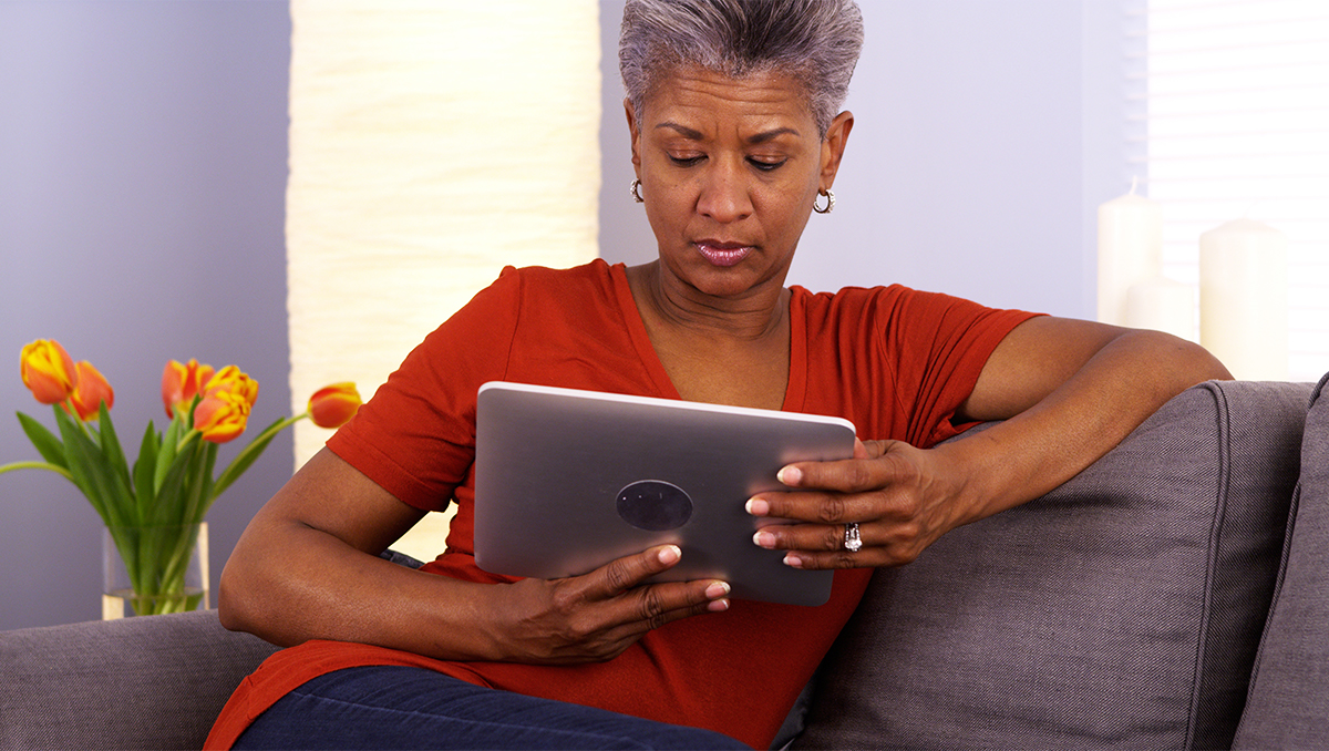 A woman sitting on a couch looks at a tablet