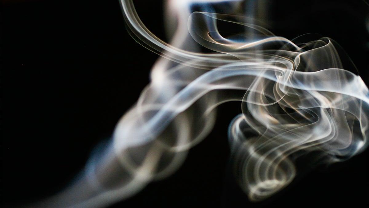 Cigarette smoke unfurls across a black background