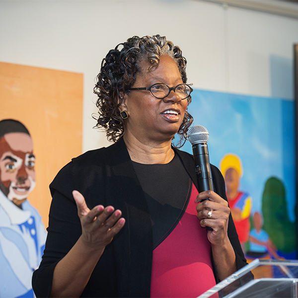 Lucile Adams-Campbell speaks into a microphone at a podium