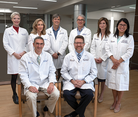 A group of doctors in their white coats stand together in a hospital setting