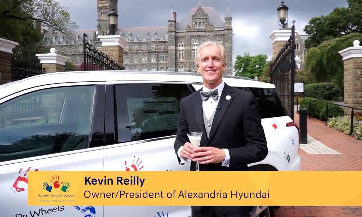 Kevin Reilly, owner/president of Alexandria Hyundai, holds a champagne glass filled with milk before the Hyundai Hope on Wheels car parked on Georgetown's campus