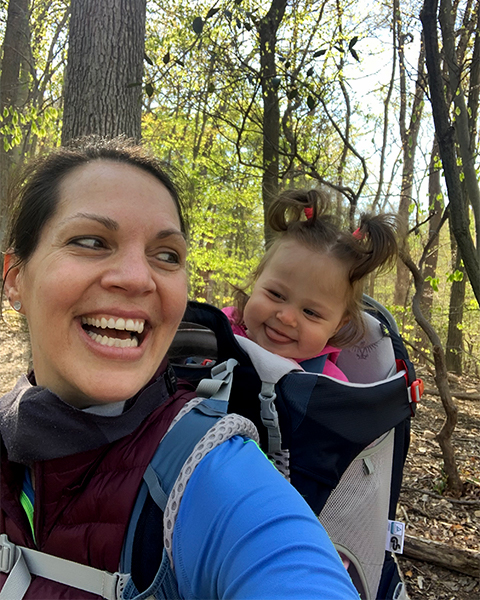 Brandi Farmer smiles back at her baby daughter who is enjoying her ride in a baby backpack carrier