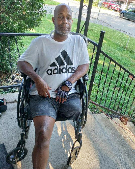Clifford Mitchiner in a wheelchair on his front porch